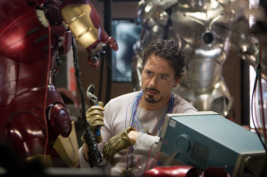 Tony Stark surrounded by different versions of his armor